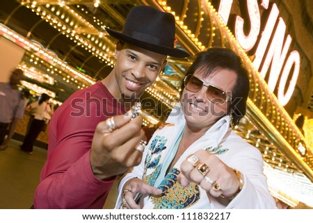 African American man standing with Elvis impersonator