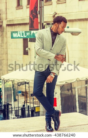 African American Man street fashion in New York, wearing gray blazer, black pants, leather shoes, wristwatch, crossing arms, legs, face with beard, looking down, thinking. Retro filtered look. - stock photo