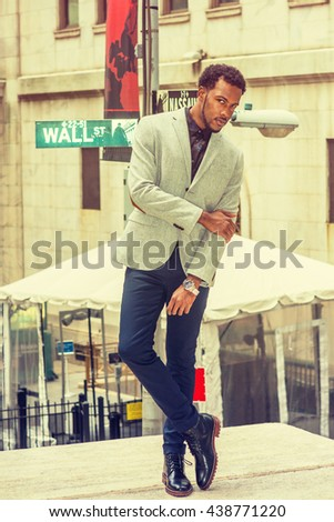African American Man street fashion in New York, wearing gray blazer, black pants, leather shoes, wristwatch, crossing arms, legs, face with beard, tilting head, looking at you. Retro filtered look. - stock photo