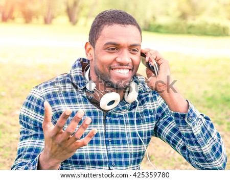 African american man talking on phone with gesture outside - Young university student  guy with positive attitude using mobile in city park - Concept of communication with modern electronic devices  - stock photo