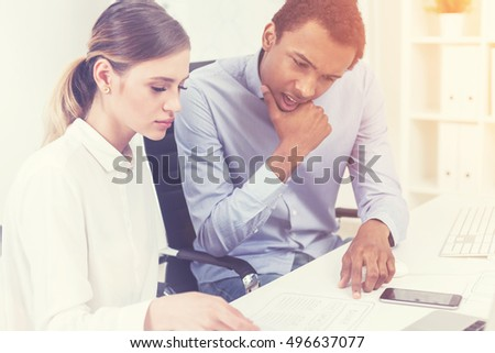 African American man thinking deeply looking at his colleague's notes. Concept of brainstorming. Toned image