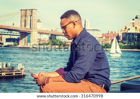 African American Man traveling in New York. Wearing blue shirt, brown pants, glasses, bracelets, a college student sitting at harbor, checking message on mobile phone. Boat, bridge on background. - stock photo