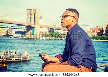 African American Man traveling in New York. Wearing blue shirt, brown pants, glasses, bracelets, a college student sitting at harbor, checking message on mobile phone, thinking. Bridge on background.  - stock photo