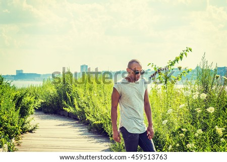 African American man traveling in New York, wearing gray short sleeve T shirt, black jeans, sunglasses, standing on remote road with green grasses by Hudson River under sun in hot summer, thinking.