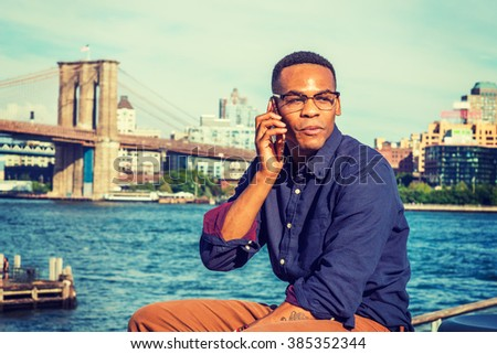 African American Man traveling, working in New York. Wearing blue shirt,, glasses, a college student sitting by river, talking on phone, smiling, amused by news. Brooklyn bridge on background.  - stock photo