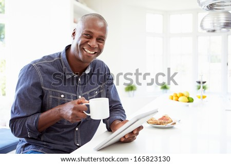 African American Man Using Digital Tablet At Home - stock photo