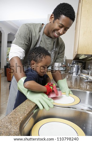 African American man washing dishes with son helping - stock photo