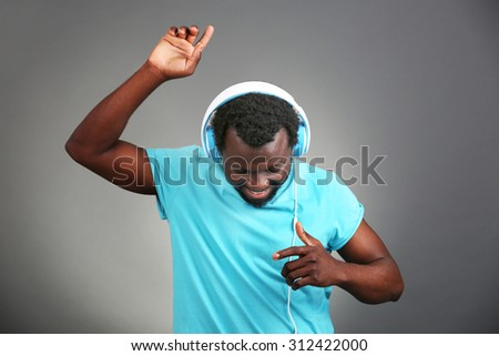 African American man with headphones on grey background - stock photo