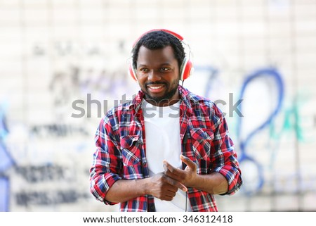 African American man with headphones outdoors