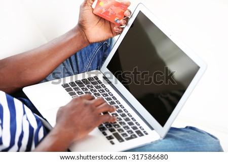 African American man with laptop and credit card on sofa