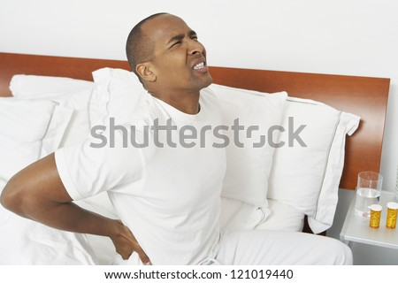 African American man with severe backache sitting on bed - stock photo