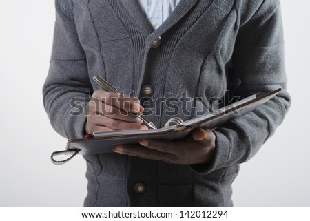 African-American man writes in a notebook