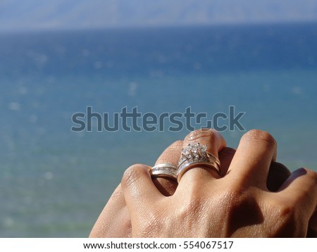 african american married couple holding hands by the pacific ocean - African Wedding Rings