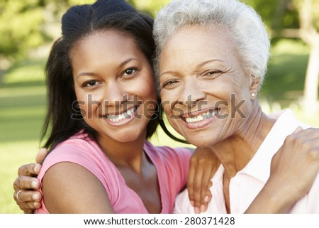 African American Mother And Adult Daughter Relaxing In Park