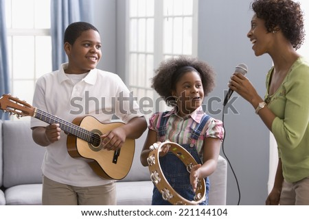African American mother and children playing instruments - stock photo