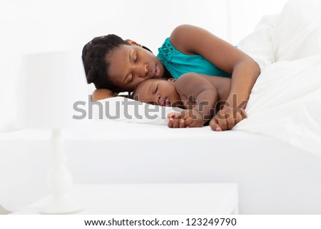 african american mother sleeping with baby boy - stock photo