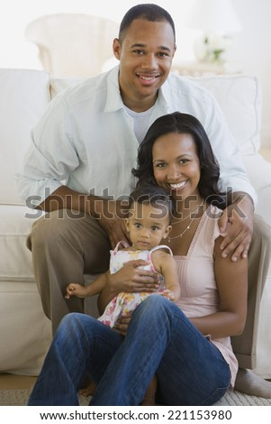 African American parents and baby in living room - stock photo
