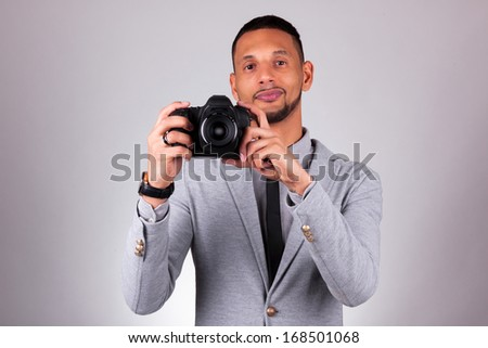 African american photographer holding a dslr camera, over gray background - Black people