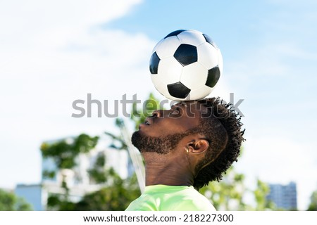 African-American player balancing soccer ball on his head - stock photo
