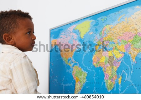 African american preschool boy in classroom with world map