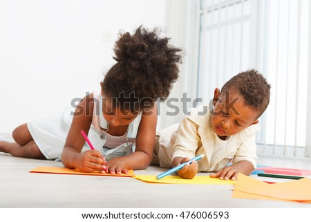 African american preschoolers drawing on the floor