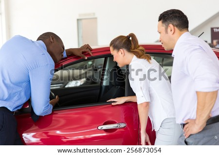 african american salesman showing new car to a couple in showroom - stock photo