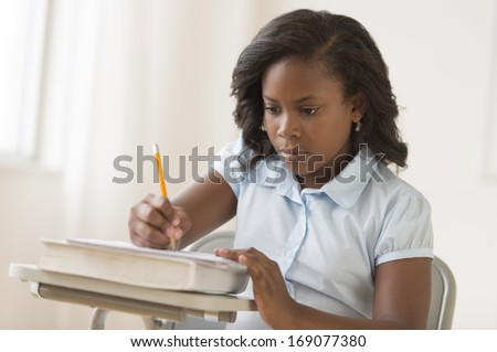 African-American schoolgirl writing notes in notepad at classroom desk - stock photo