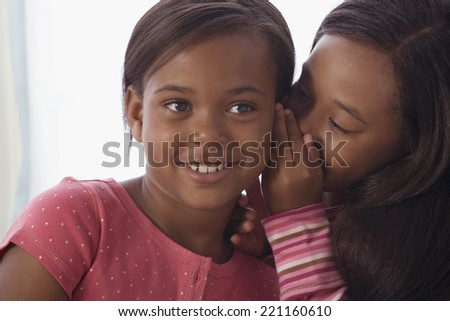 African American sisters telling secret - stock photo