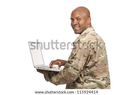 African American soldier looks over his shoulder while typing on a computer - stock photo
