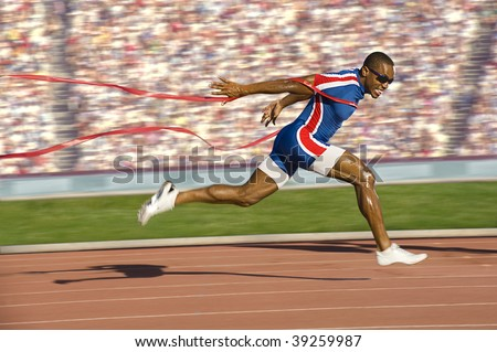 African American sprinter crossing the finish line and breaking the tap. Horizontally framed shot.