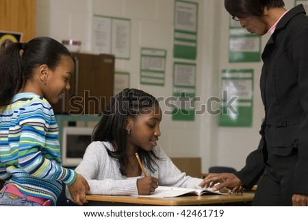 African American student gets help from teacher while another student look at the math problem - stock photo