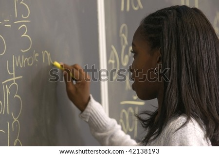 African American student writing a math problem on the chalkborad - stock photo