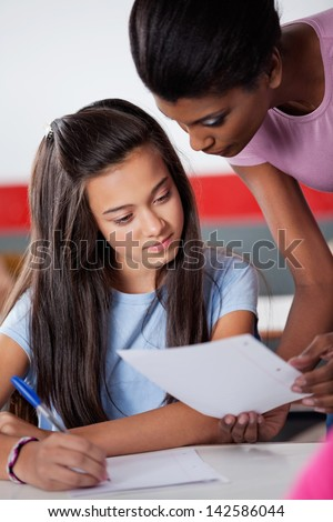 African American teacher assisting teenage schoolgirl during examination at desk in classroom - stock photo