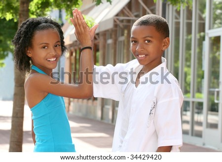 African-American Teenager Friends doing a high five, city street