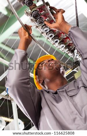 african american textile industrial technician repairing weaving machine - stock photo