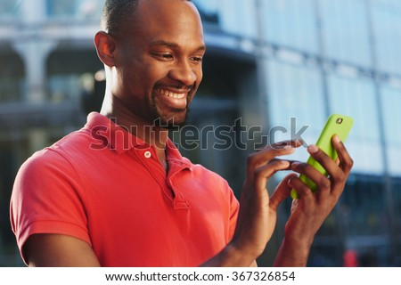 African American using smart phone in busy city to stay connected using social media - stock photo