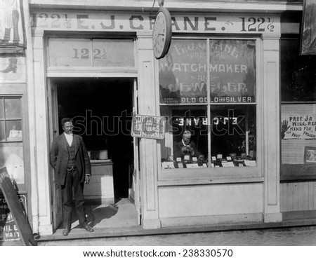 African American watchmaker, original title: 'E.J. Crane, watchmaker and jewelry store with man working in window and man standing in doorway', Richmond, Virginia, photograph, 1899.