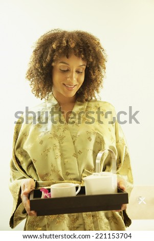 African American woman carrying tea tray - stock photo