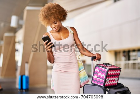 african american woman checking flight on smartphone at airport with luggage