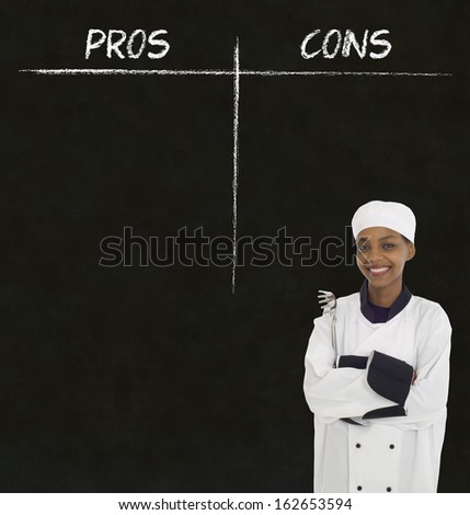 african american woman chef holding utensil with chalk pros and cons on blackboard background - stock photo