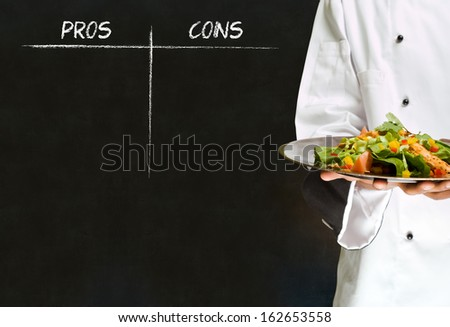 african american woman chef with chalk pros and cons on blackboard background - stock photo