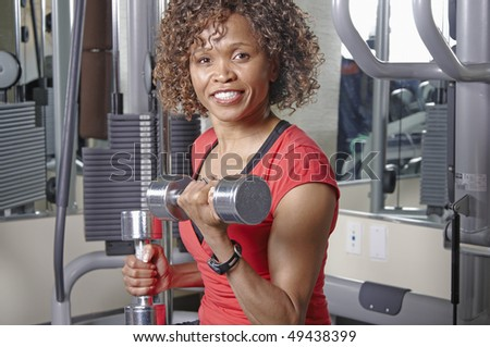 African American woman doing bicep curls in a gym - stock photo