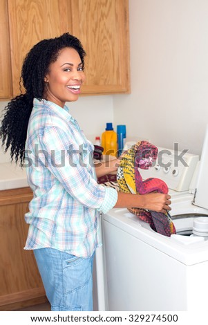 African american woman doing laundry - stock photo