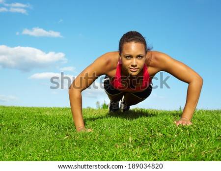 African American Woman Doing Push Ups In Park. Copy space, color image, mixed race woman working out horizontal shot. - stock photo