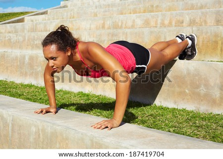 African American Woman Doing Push Ups In Park On Steps. Copy space, color image, mixed race woman working out horizontal shot. - stock photo