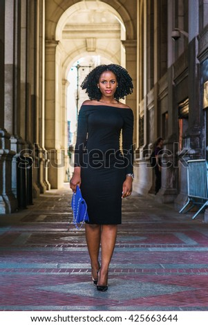 African American Woman Fashion in New York. Wearing long sleeve, slim, off shoulder dress, carrying blue bag, young lady walking on vintage style, narrow street, going to work. Retro filtered look. - stock photo