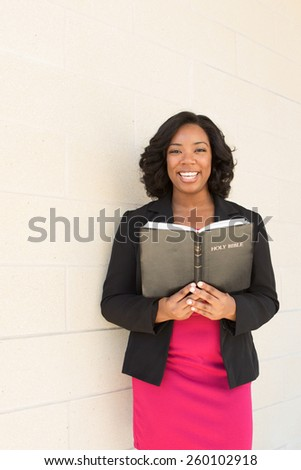 African American woman holding a Bible looking at the camera and smiling. - stock photo
