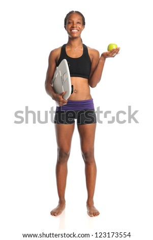 African American woman holding apple and scale standing isolated over white background - stock photo