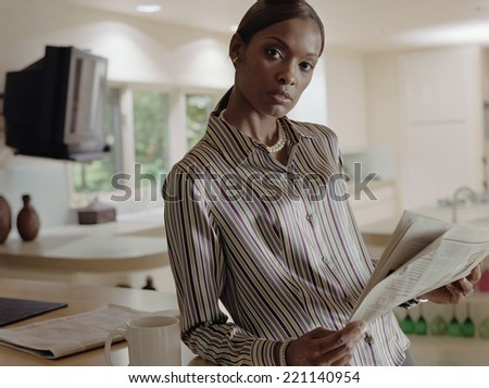 African American woman holding newspaper - stock photo