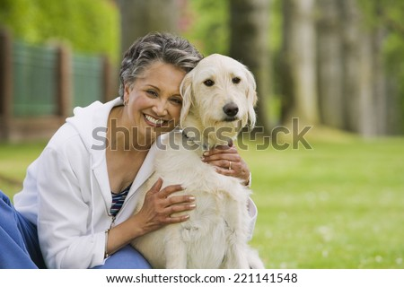 African American woman hugging dog - stock photo
